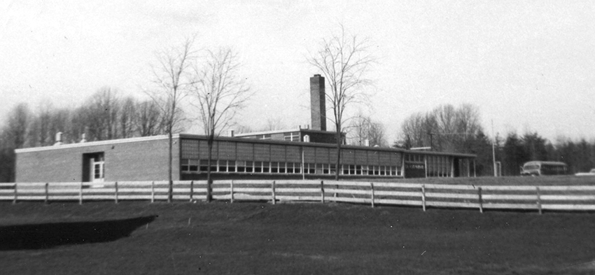 Black and white photograph of Lemon Road Elementary School taken in 1958. Idylwood Road is much narrower than in the present day and there are less trees. A white fence separates the school property from neighboring homes.