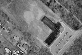Black and white aerial photograph of Lemon Road Elementary School taken in 1972. Lemon Road is an L-shaped building. The forested area in the previous image is gone. Also, houses have been constructed on what used to be the surrounding farm fields.