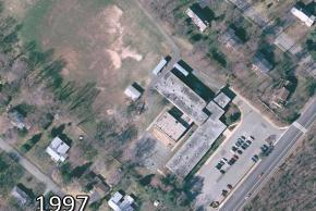 Color aerial photograph of Lemon Road Elementary School taken in 1997. The building has had two additions since the last image. The bend in the L-shaped area has been enclosed by a large rectangular section. Portable classrooms are visible in the rear of the building.