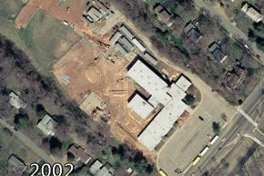 Color aerial photograph of Lemon Road Elementary School taken in 2002. Major construction work is taking place. A new addition is being built onto the rear of the school. The fields out back are packed full of construction trailers. The outlines of the cinderblock walls are visible rising from the dirt.