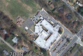 Color aerial photograph of Lemon Road Elementary School taken in 2009. The addition is complete, linking all areas of the building together. The parking lot has been extended into the rear of the building and a new playing field and playground have been added.