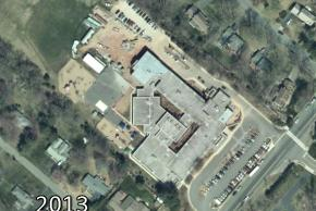 Color aerial photograph of Lemon Road Elementary School taken in 2013. More construction appears to be underway as the playing fields now have rows of cars and portable buildings on them.